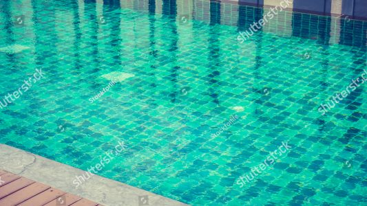 stock-photo-beautiful-outdoor-swimming-pool-in-hotel-resort-filter-effect-470240051