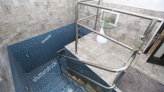 stock-photo-blue-tiled-mikveh-or-ritual-bath-with-railing-and-steps-is-used-by-jews-for-purification-1011258034