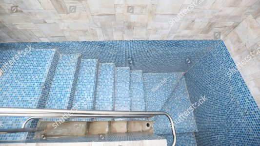stock-photo-blue-tiled-mikveh-or-ritual-bath-with-railing-and-steps-is-used-by-jews-for-purification-1011258061