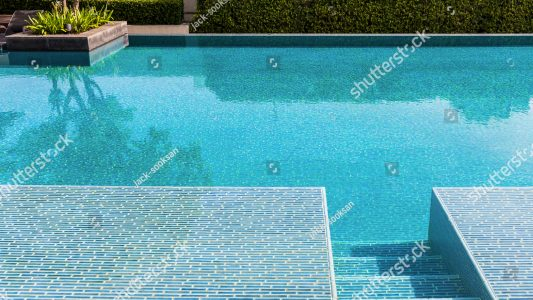 stock-photo-swimming-pool-made-by-mosaic-tiles-with-small-stairs-inside-the-clear-blue-water-which-not-moving-455276350